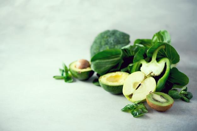 Verduras y frutas verdes orgánicas en fondo gris.