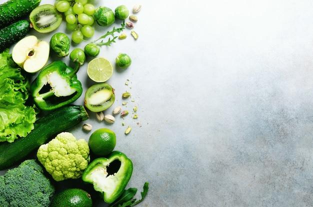 Verduras y frutas verdes orgánicas en gris. copia espacio, plano, vista superior. manzana verde, lechuga, calabacín, pepino, aguacate, col rizada, lima, kiwi, uvas, plátano, brócoli