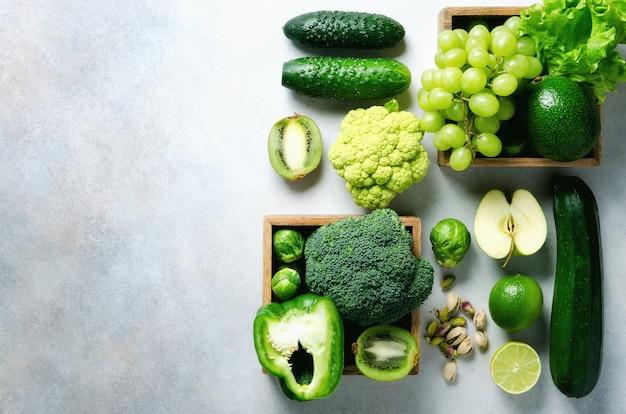 Verduras y frutas verdes orgánicas en gris. manzana verde, lechuga, calabacín, pepino, aguacate, col rizada, lima, kiwi, uvas, plátano, brócoli