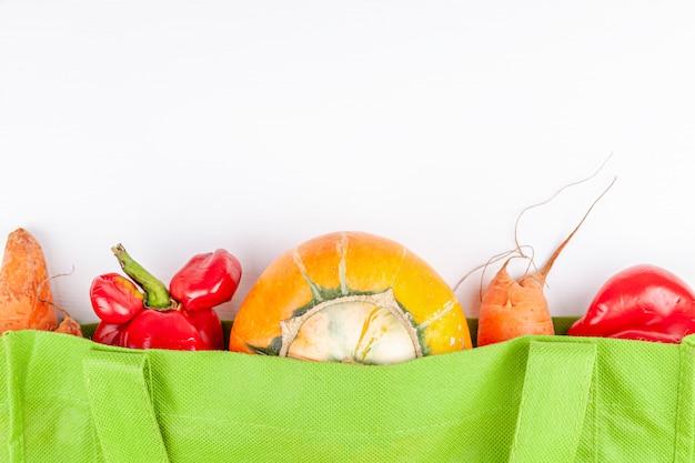 Verduras de granja orgánicas feas y de moda con mutaciones en una bolsa de compras reciclable