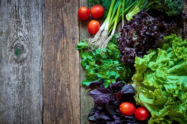 Verduras y hierbas frescas sobre una vieja superficie de madera rugosa