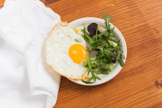 Verduras de hoja y medio huevos fritos en un plato sobre el escritorio de madera