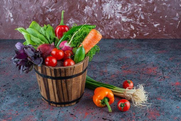 Verduras mixtas en un balde, sobre el fondo de mármol.
