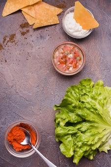 Verduras entre nachos con salsas y chile.