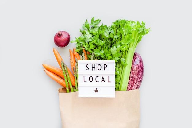 Verduras orgánicas frescas en una bolsa de compras de papel artesanal ecológico con el texto shop local en la caja de luz