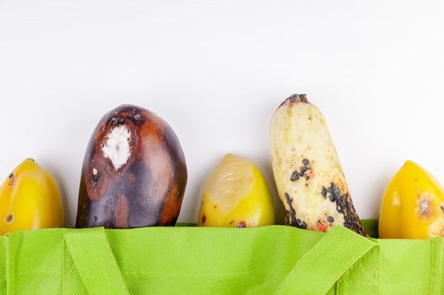 Verduras orgánicas podridas en bolsa de compras reutilizable verde sobre fondo blanco.
