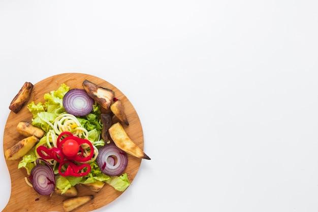 Verduras picadas y patata asada en tabla de cortar de madera sobre fondo blanco