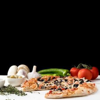 Verduras y pizza en el escritorio