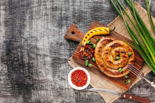 Verduras a la plancha y salchicha espiral con pimienta roja en grano.