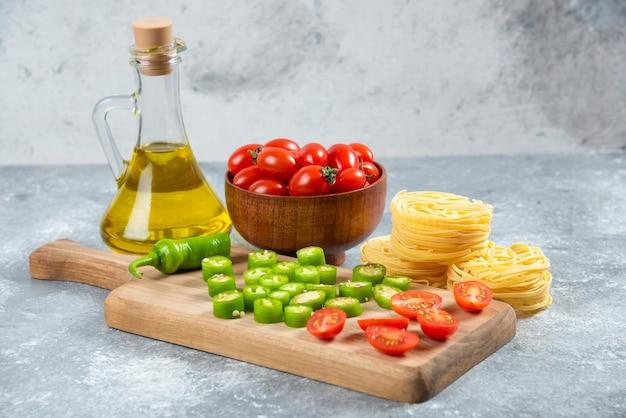 Verduras en rodajas, aceite de oliva y nidos de pasta sobre fondo de mármol.