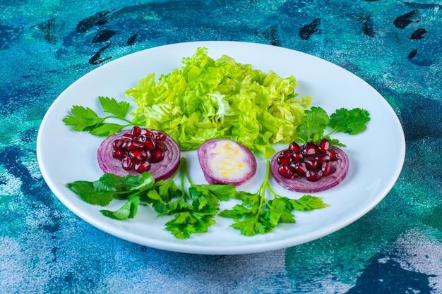 Verduras en rodajas y arilos de granada en un plato