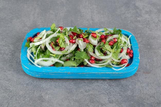 Verduras en rodajas, cebollas y semillas de granada en placa azul. foto de alta calidad