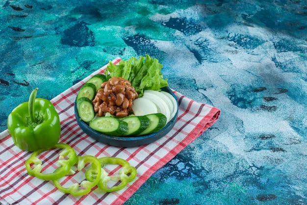 Verduras en rodajas y frijoles horneados en una placa de madera sobre una toalla, sobre la mesa azul.