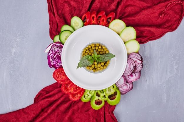 Verduras en rodajas y hierbas en un plato blanco sobre el mantel rojo.