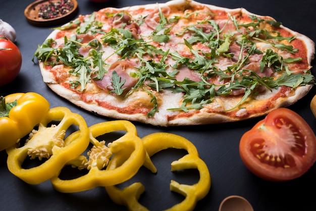 Verduras saludables y pizza de rúcula sobre encimera de cocina