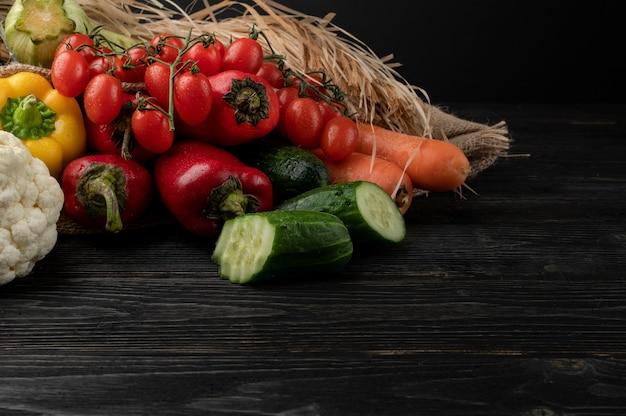 Verduras sobre un fondo de madera oscura, bellamente decorado bodegón de verduras.