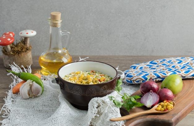 Verduras sobre tabla de madera con tazón de fideos y botella de aceite