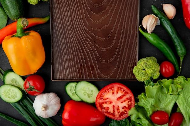 Verduras con tabla de cortar en mesa granate
