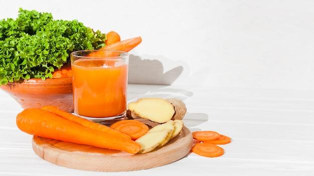 Verduras y vegetación con zumo en mesa.