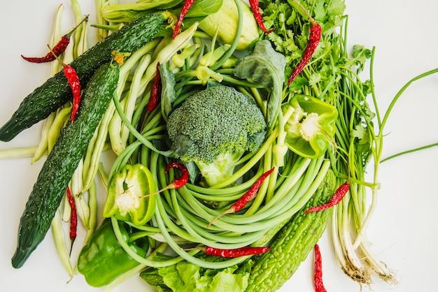 Verduras verdes con chile rojo sobre fondo blanco
