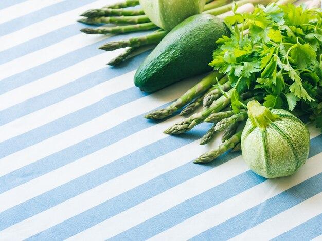 Verduras verdes en mantel a rayas