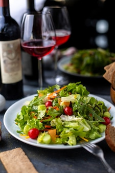 Verduras verdes en rodajas junto con vino tinto dentro de un plato blanco