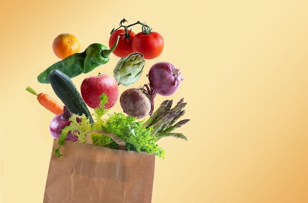 Verduras volando en bolsa de papel reciclable con espacio de copia