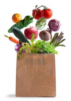 Verduras volando en bolsa de papel reciclado