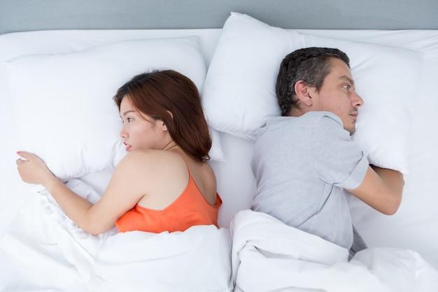 Vergüenza joven pareja acostada en la cama volver a la espalda