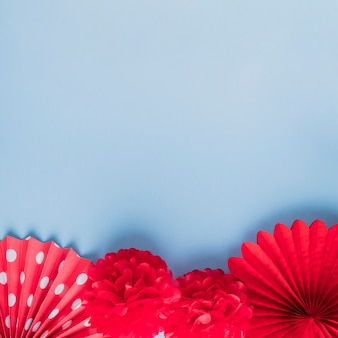 Veridad de flores de origami falso rojo sobre superficie azul