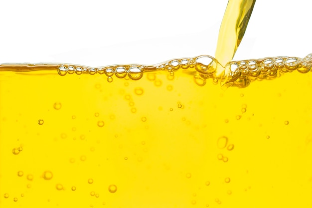 Verter aceite amarillo y burbuja sobre fondo blanco