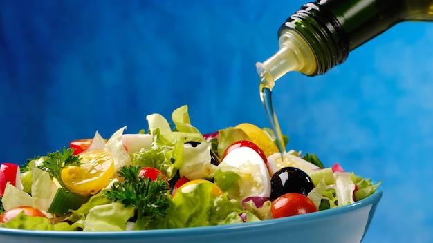 Verter el aceite de oliva de la botella en ensalada de verduras, alimentos saludables y dietéticos a partir de ingredientes frescos en un tazón sobre fondo azul.
