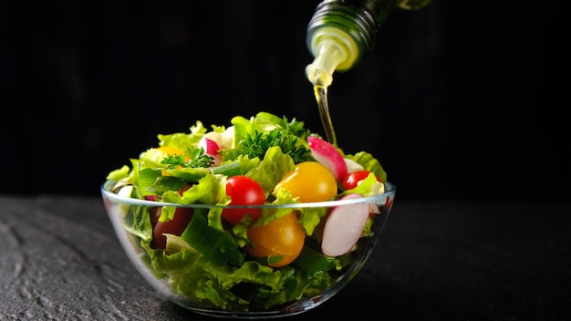 Verter el aceite de oliva de la botella en ensalada de verduras, alimentos saludables y dietéticos a partir de ingredientes frescos en un tazón de vidrio sobre fondo negro