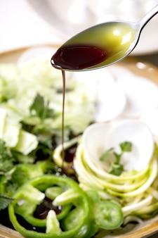 Verter aceite de semilla de calabaza en hierbas y verduras crudas verdes frescas