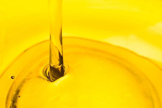 Verter el aceite en un tazón, lubricante de coche vegetal oliva