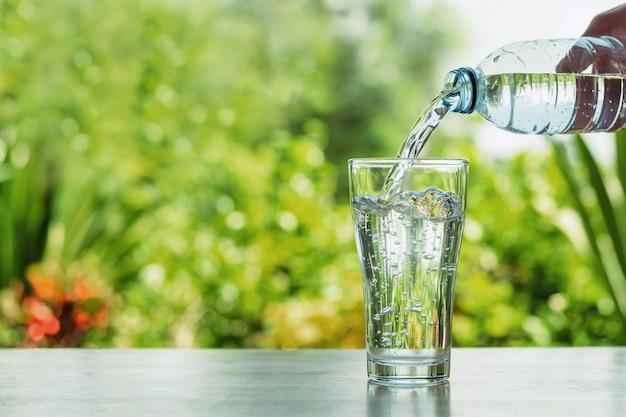 Verter agua de botella en vaso sobre fondo de naturaleza bokhe