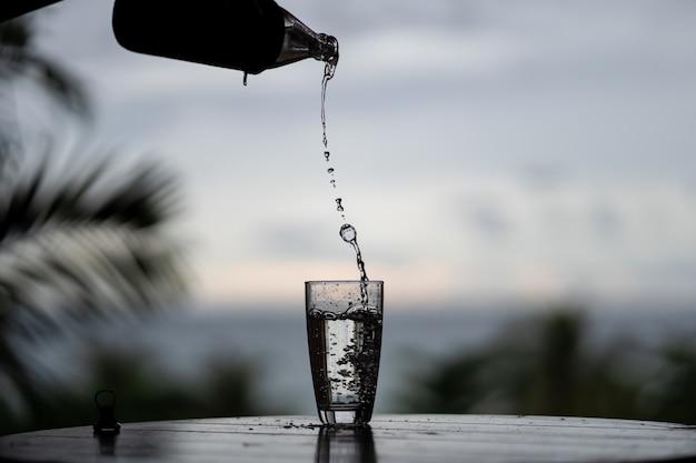Verter el agua de la botella en el vaso sobre fondo de naturaleza