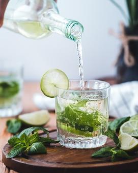 Verter agua con cal en un vaso de vidrio