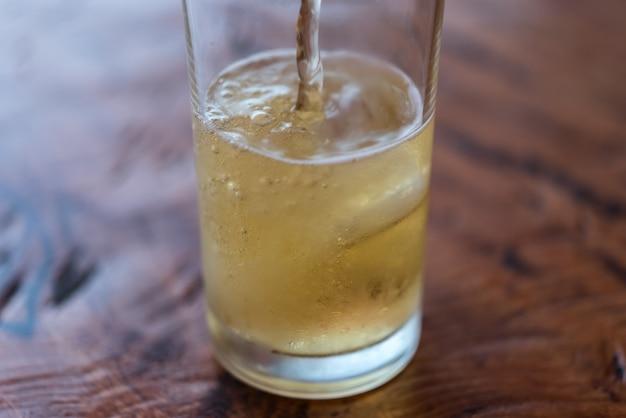 Verter agua de cerveza en un vaso con hielo y espuma
