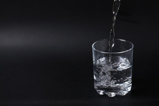 Verter agua en un vaso medio lleno.