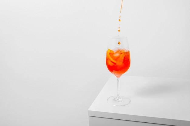Verter el aperol en copa de vino con hielo sobre fondo blanco.