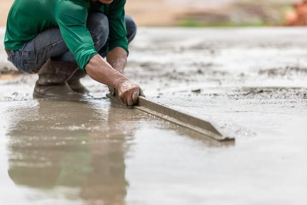 Verter y barrer el cemento húmedo en el piso en proceso de construcción de viviendas
