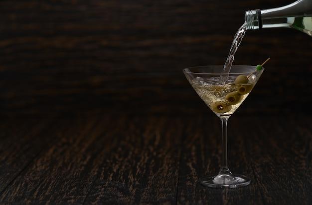 Verter la bebida alcohólica de la botella en el vaso contra la mesa de madera.