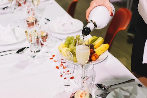 Verter un brindis de champán en una fiesta de celebración de la boda