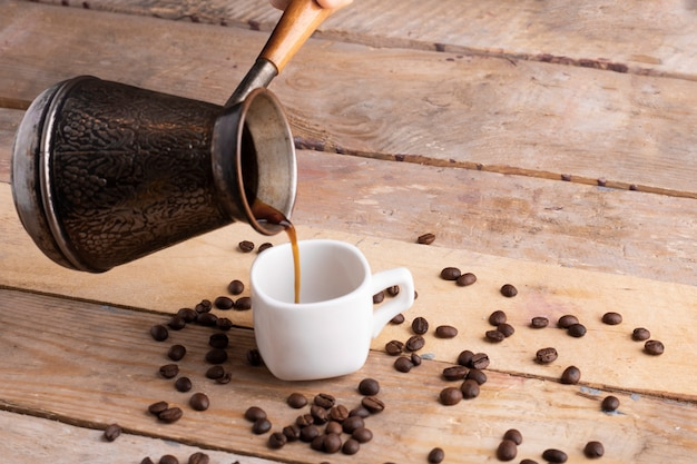 Verter café en una taza blanca, semillas alrededor