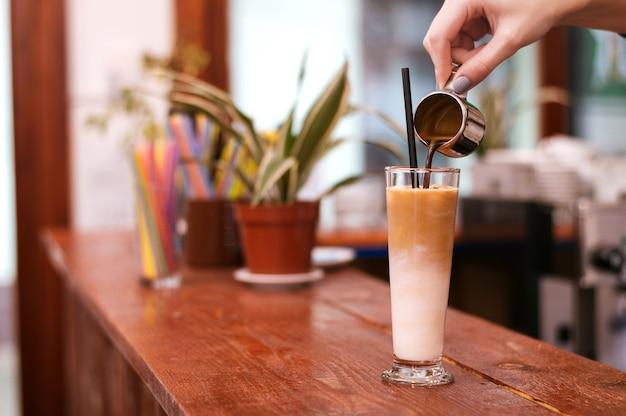 Verter el café en una taza de café, preparando capuchino.