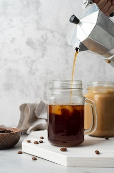 Verter el café en la taza de cerca