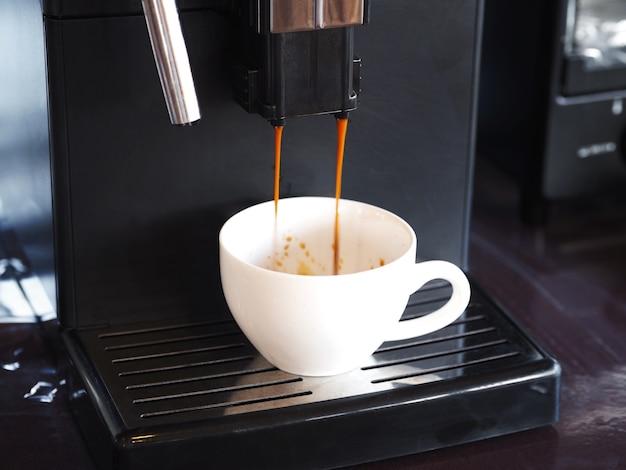 Verter el café vertido desde la máquina del fabricante en tazas blancas en el restaurante o ccafe