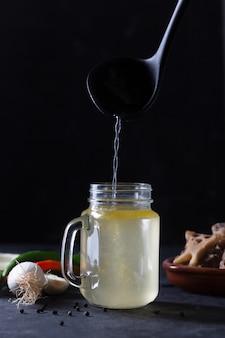 Verter el caldo de hueso de ternera casero en frasco de vidrio en un espacio negro