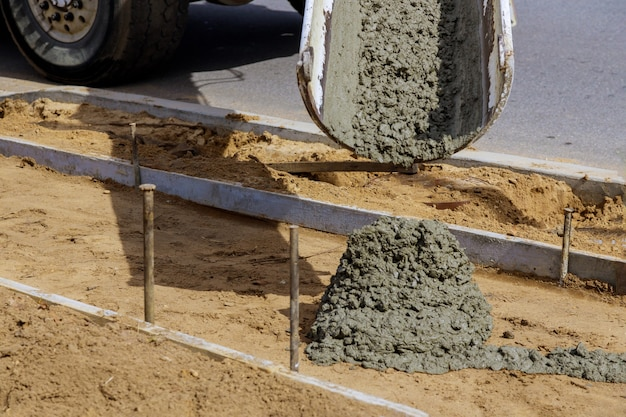 Verter cemento durante la acera nueva de hormigón
